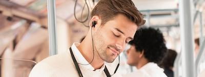 Hình ảnh phong cách sống chụp một người đàn ông đang dùng tai nghe WI-1000XM2 trên phương tiện công cộng