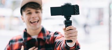 Hình ảnh một người đang quay phim chính mình bằng ZV-E10 gắn báng tay cầm