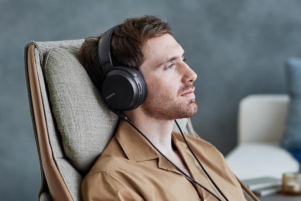 Một người đàn ông thư giãn khi đeo đệm tai thoải mái của MDR-M7M2