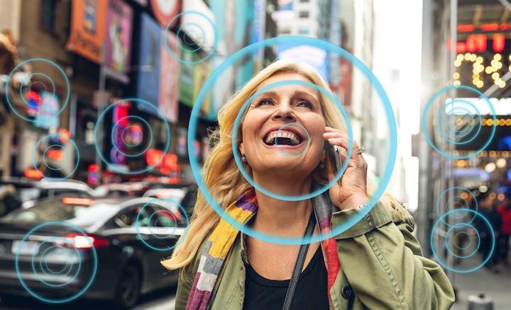 Người phụ nữ giữa đường phố đông đúc thể hiện cách Voice Zoom 2 giúp giọng nói dễ nghe hơn