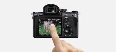 Hình ảnh minh họa mặt sau máy ảnh với ngón tay mô phỏng thao tác cảm ứng trên màn hình LCD