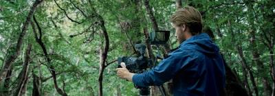 Hình ảnh người đàn ông sử dụng máy ảnh gắn micro ngoài và màn hình ngoài trên nền lá cây ở xa