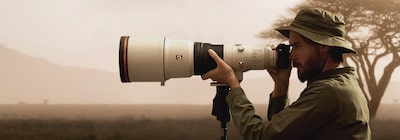 Hình ảnh người đàn ông nhìn qua máy ảnh gắn chân máy được lắp một ống kính chụp siêu tele