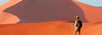 Hình ảnh một người đàn ông quay lưng lại với máy ảnh trên nền cồn cát màu đỏ