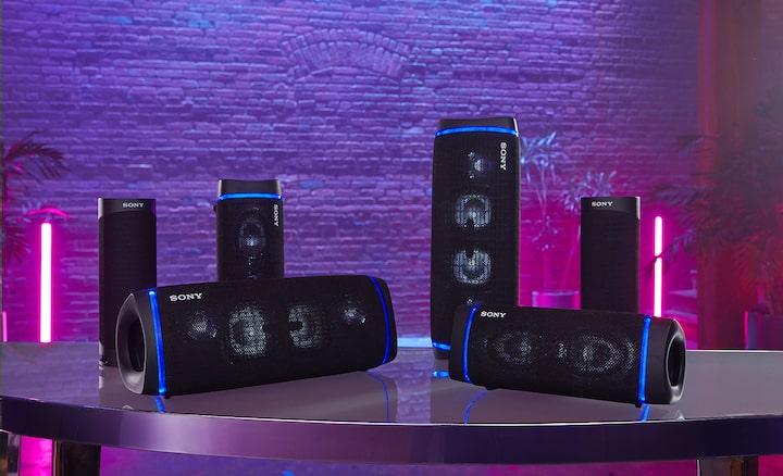 SRS-XB43 đặt trên bàn cùng nhiều model tương thích Bluetooth đang bật đèn tiệc